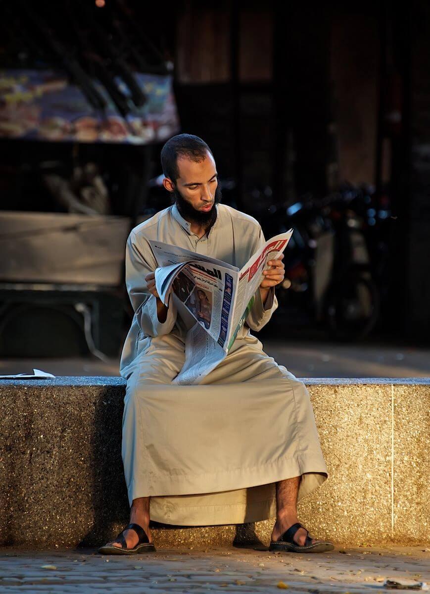 Man dressed in djellaba reading newspaper