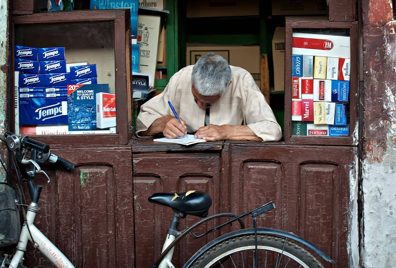 Shop keeper writing a ledger; Marrakech