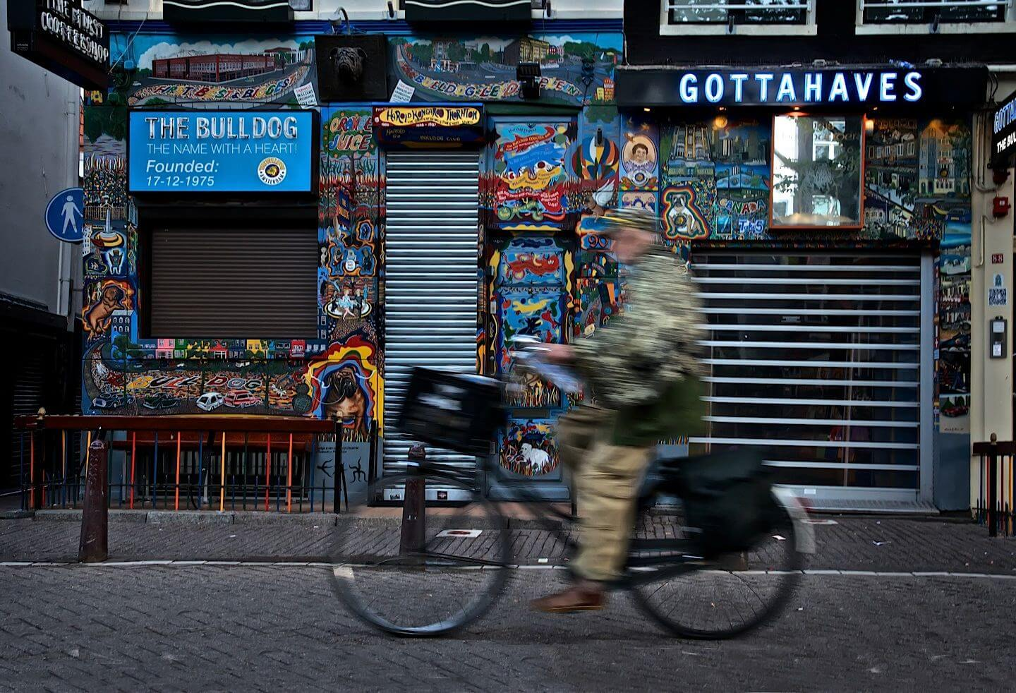 Man riding a bicycle along a Gottahaves Coffeeshop in Amsterdam