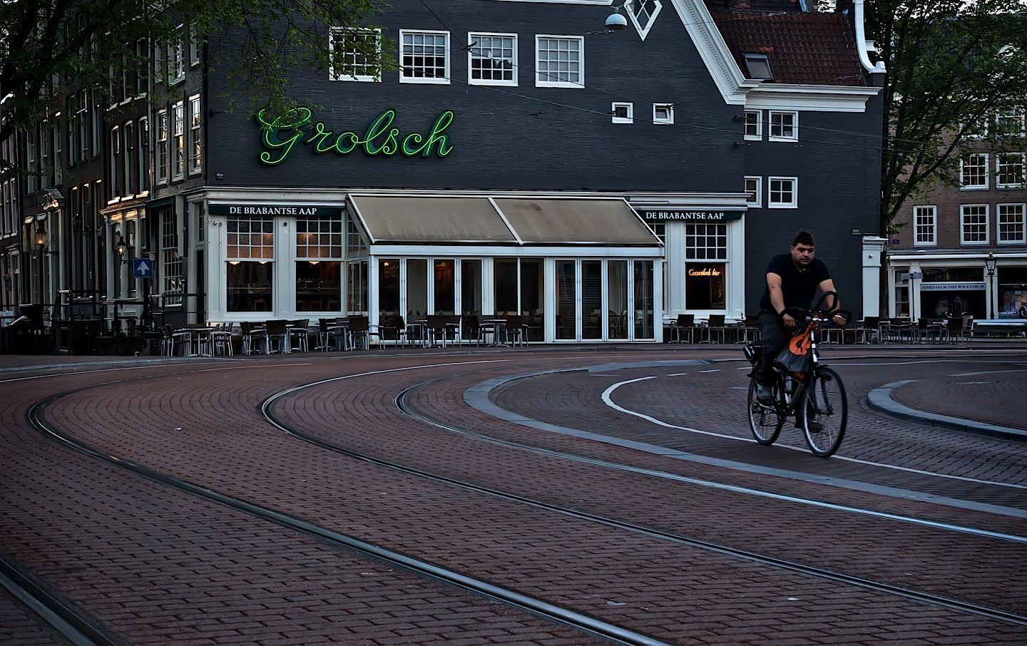 Man on a bicycle on an empty Amsterdam street